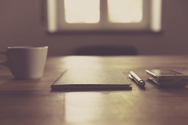 デスクに置かれたスマホ、ノート、コーヒーのイメージ