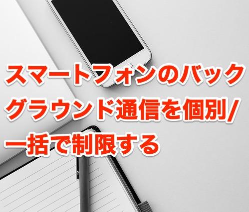 スマートフォンのバックグラウンド通信を個別/一括で制限すると書かれた背景にノートとスマホが写る画像